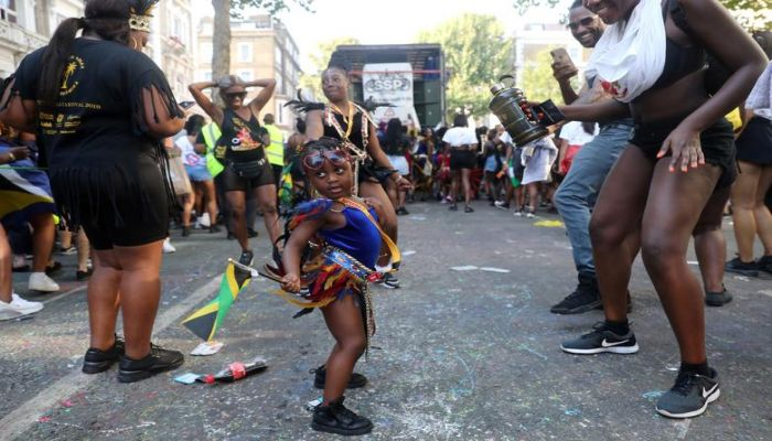 A child reveller dances, holding the Jamaican flag, at the Notting Hill Carnival in London, Britain August 25.  Photo: Collected