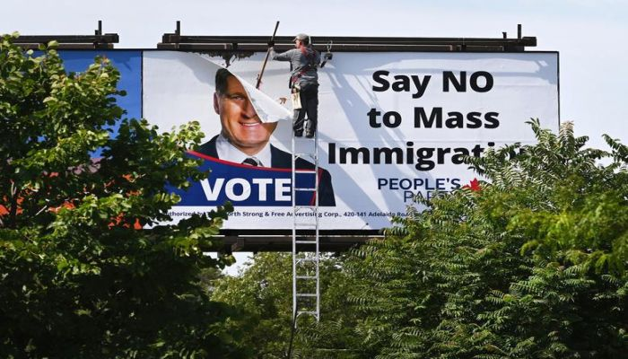 """A worker removes a billboard featuring the portrait of People's Party of Canada leader Maxime Bernier and its message """"Say NO to Mass Immigration"""" in Toronto, Canada August 26. Photo: Collected"""