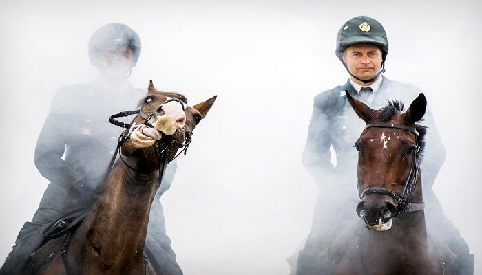 Members of the Dutch Royal Guard guide their horses through clouds of thick smoke and gunfire on the beach of Scheveningen, near The Hague, to prepare them for the Prinsjesdag parade on 17 September. Photo: KOEN VAN WEEL