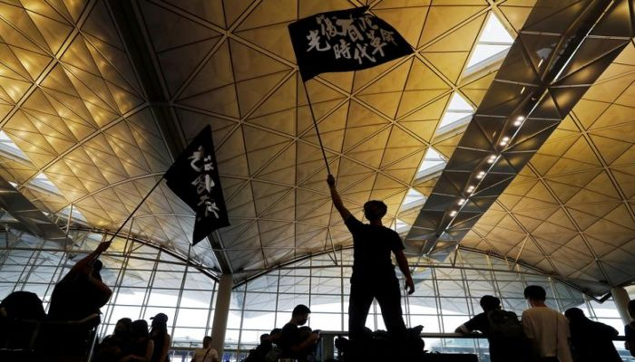 "Anti-extradition bill protesters wave flags with Chinese calligraphy that reads ""Liberate Hong Kong, the revolution of our times"", at a mass demonstration at Hong Kong International Airport, in Hong Kong, August 12, 2019. REUTERS"