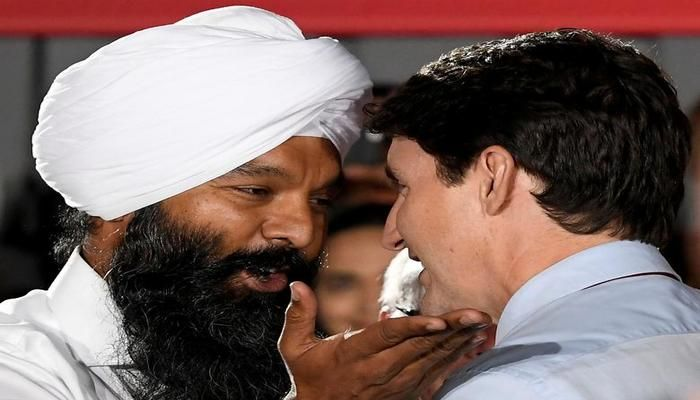 """Canada's Prime Minister Justin Trudeau greets Surrey-Centre candidate Randeep Sarai at an election campaign rally in British Columbia, Canada September 24, 2019. Trudeau had been running neck-and-neck with Conservative leader Andrew Scheer until Time magazine published a picture of Trudeau in dark makeup and a turban at a 2001 """"Arabian Nights"""" party, when he was a 29-year-old teacher. Two other images and a video of him in blackface later emerged. REUTERS"""