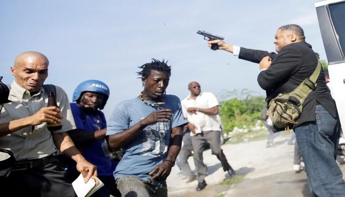 People run as Haiti's Senator Jean Marie Ralph Fethiere fires a gun in the air, injuring Associated Press photographer Chery Dieu-Nalio, while facing angry opposition supporters in the parking lot of the Haitian Parliament and Senate, as the government attempted to confirm the appointment of nominated Prime Minister Fritz William Michel, in Port-au-Prince, Haiti September 23, 2019. The shooting came at a time when Haitians have become increasingly angry at shortages of fuel and food. Fethiere later told a local radio station he was acting in self-defence. REUTERS