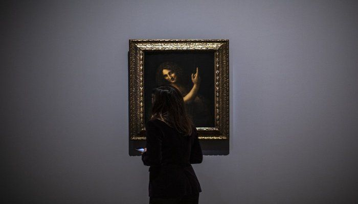 A journalist studies Saint Jean Baptiste artwork by Leonardo da Vinci during a visit at the Louvre museum Sunday, Oct. 20, 2019 in Paris. A unique group of artworks is displayed at the Louvre museum in addition to its collection of paintings and drawings by the Italian master. The exhibition opens to the public on Oct. 24, 2019. (AP Photo)