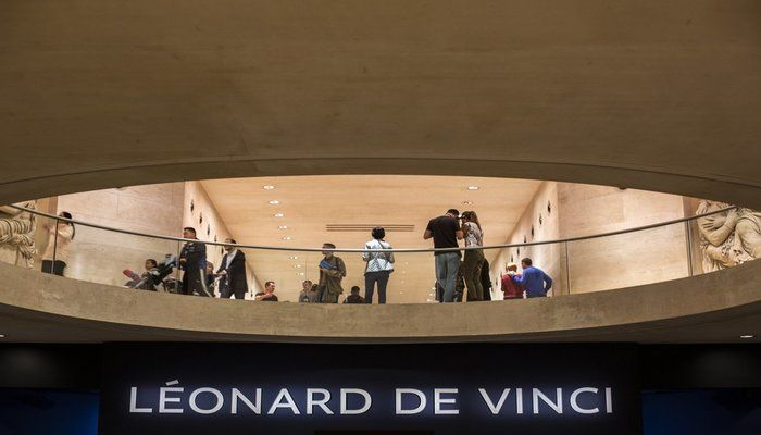 Visitors stand next to Leonardo da Vinci exhibition at the Louvre museum Sunday, Oct. 20, 2019 in Paris. A unique group of artworks is displayed at the Louvre museum in addition to its collection of paintings and drawings by the Italian master. The exhibition opens to the public on Oct.24, 2019. (AP Photo)