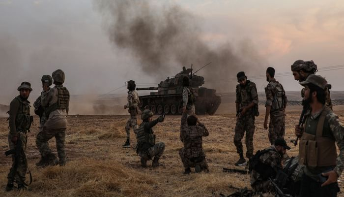 Turkish soldiers and Turkey-backed Syrian fighters gather on the northern outskirts of the Syrian city of Manbij, near the Turkish border, on Oct. 14, 2019. Photo: AFP.