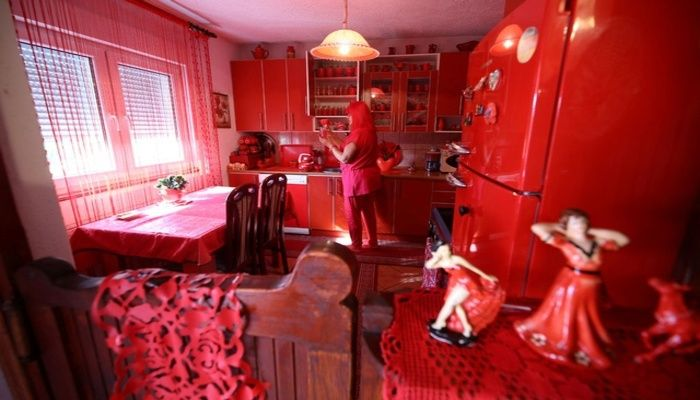 Zorica Rebernik, obsessed with the red color, stands in the kitchen inside her house in the village of Breze near Tuzla, Bosnia and Herzegovina October 16, 2019. Reuters