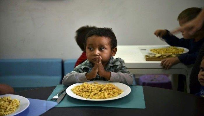 A child prays before eating at the Kapuy Foundation shelter which supports children abandoned, or with serious health problems, including undernourishment in Venezuela. Photo: AFP
