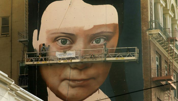 Andres Petreselli paints a mural on the side of a building depicting Swedish teen climate activist Greta Thunberg, Friday, Nov. 8, 2019, in San Francisco. Photo: AP
