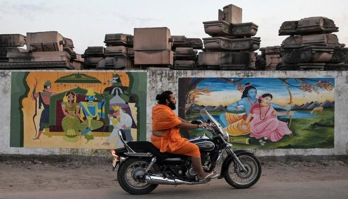 A Hindu priest rides past a workshop where the pillars that Hindu nationalist group Vishva Hindu Parishad (VHP) say will be used to build a Ram temple at the disputed religious site are kept, in Ayodhya, India, October 22, 2019. Photo: REUTERS