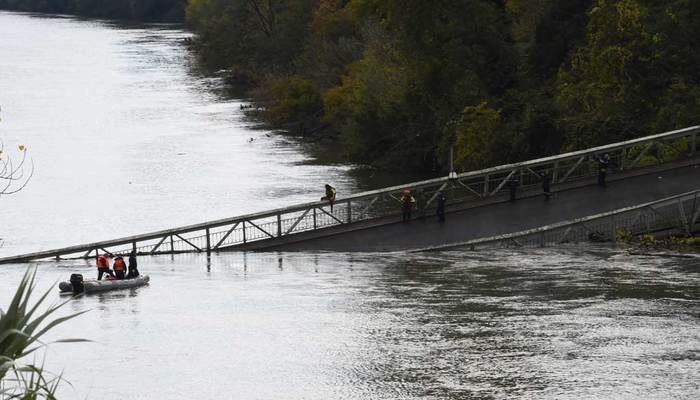 Rescuers sail near a suspension bridge which collapsed in Mirepoix-sur-Tarn, near Toulouse, France on November 18, 2019 | Photo: AFP