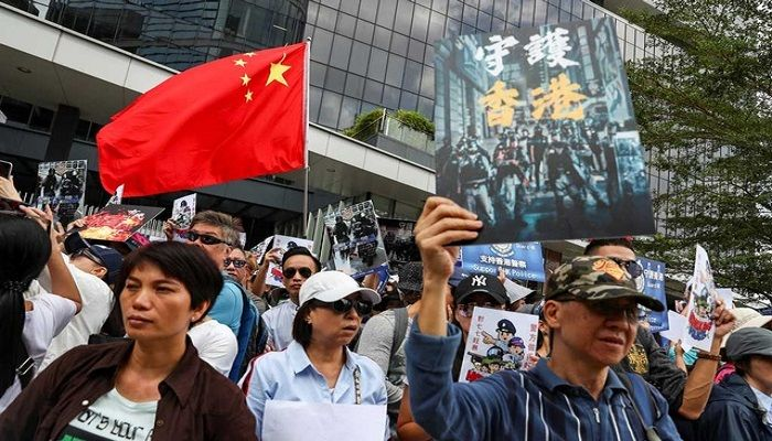 People hold a China national flag and signs as they participate in a pro-government rally to show their support for the police and government at the Legislative Council (LegCo) building in Hong Kong, China, November 16, 2019. REUTERS