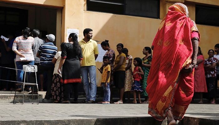 A woman walks into a line to cast her vote during the presidential election at polling station in Colombo, Sri Lanka November 16, 2019. Photo: Reuters