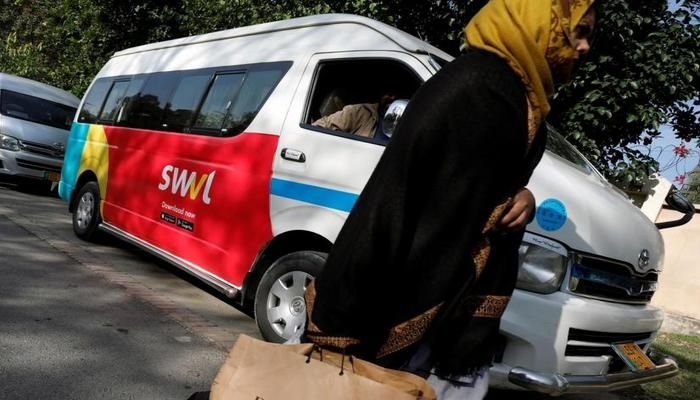 A woman walks past a vehicle with a logo of the Egyptian transport technology start-up Swvl, parked along a road in Islamabad, Pakistan, Nov 11, 2019. Photo: REUTERS