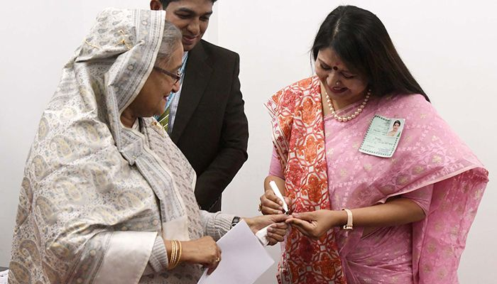 An official in charge is imposing ink on Prime Minister Sheikh Hasina after casting vote. Photo: PID