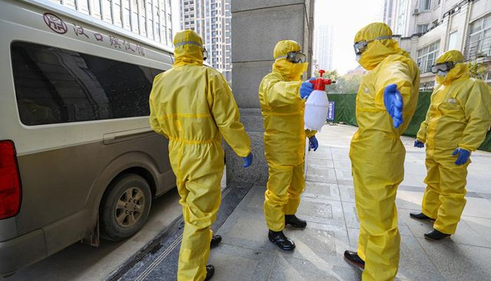 Funeral parlor staff members in protective suits help a colleague with disinfection after they transferred a body at a hospital, in Wuhan, Hubei province, China. The city of 11 million people is in a virtual lockdown and much of Hube. Photo: Reuters