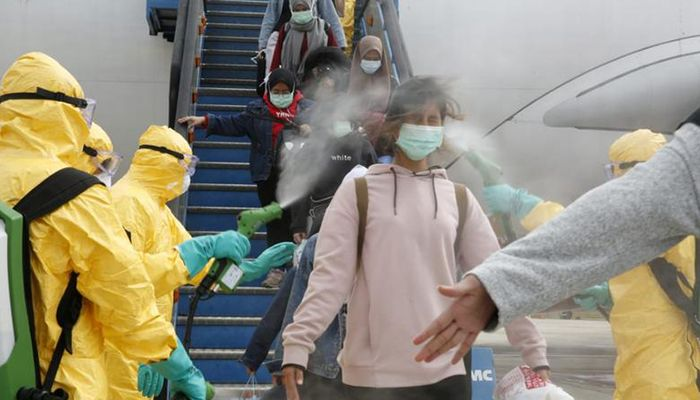 Medical officers spray Indonesian nationals with antiseptic after they arrived from Wuhan, China, the center of the coronavirus epidemic, before transferring them to be quarantined, at Hang Nadim Airport in Batam, Indonesia. Photo: Collected from Reuters