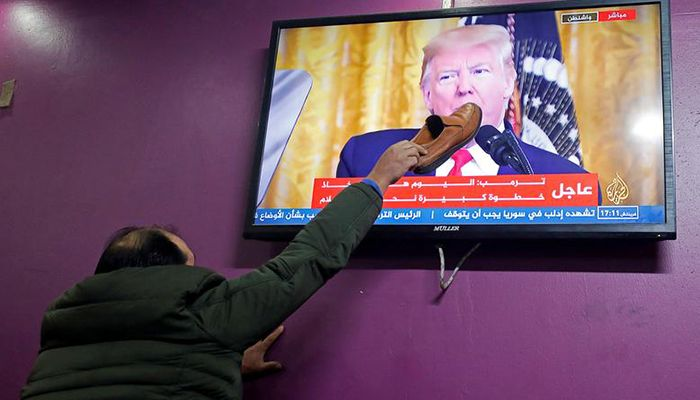 A Palestinian man places a shoe on a television screen broadcasting the announcement of U.S. President Donald Trump's Middle East peace plan, in a coffee shop in Hebron in the Israeli-occupied West Bank January 28, 2020. Photo: Collected from Reuters