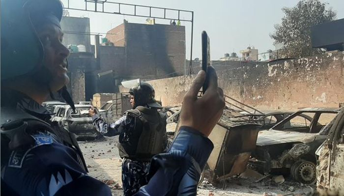 Two of the law enforcement members taking a selfie standing in the wreckage. Photo: DW