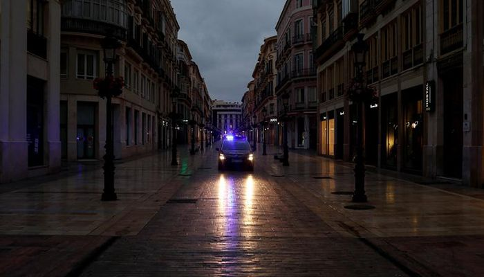 Spanish National Police officers guard the empty Larios street during the partial lockdown in downtown Malaga, southern Spain, March 15, 2020. Photo: Collected from Reuters