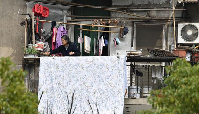 A woman places food out on a balcony to dry at a residential compound in Wuhan, the epicenter of the coronavirus outbreak, Hubei province, China, March 10, 2020. Photo: Collected from Reuters
