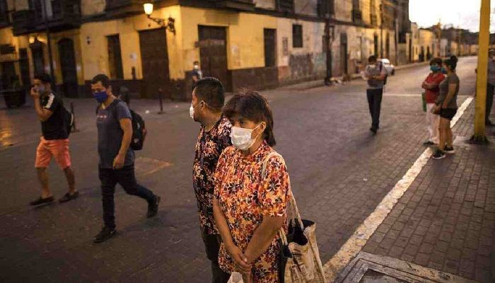 People using masks as a precaution against the spread of the new coronavirus, wait for public transportation, at a popular market in Lima, Peru. Photo: Collected from AP