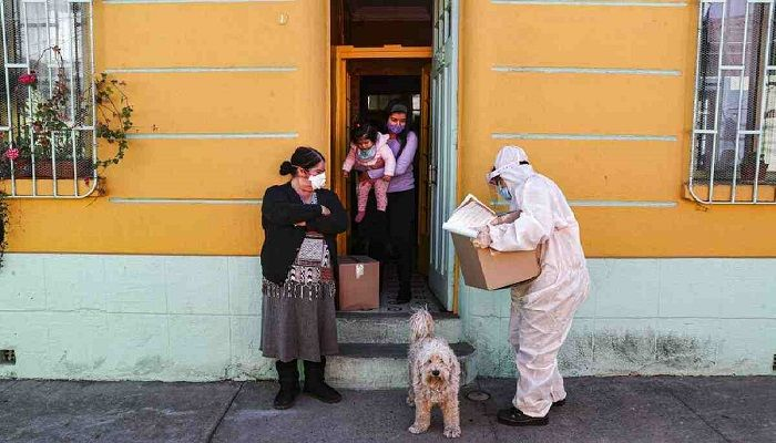 A city worker, dressed in protective gear, delivers a box of food during a mandatory quarantine ordered by the government amid the new coronavirus pandemic in Santiago. Photo: Collected from AP