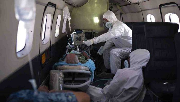 Doctor Daniel Siqueira, top, and nurse Janete Vieira monitor 89-year-old COVID-19 patient Sildomar Castelo Branco onboard an aircraft, as he is transferred from Santo Antonio do Iça to a hospital in Manaus, Brazil. Photo: Collected from AP