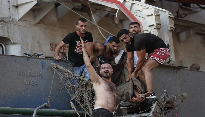 Civilians help evacuate an injured sailor from a ship which was docked near the explosion scene. Photo: Collected from AP