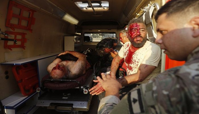 A Lebanese soldier (right) checks on injured men who sit inside an ambulance at the explosion scene. Photo: Collected from AP