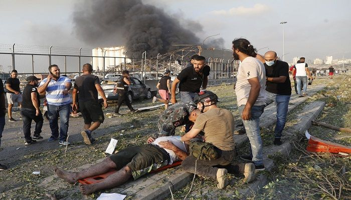 Rescue workers help an injured man at the explosion scene that hit the seaport of Beirut. Photo: Collected from AP