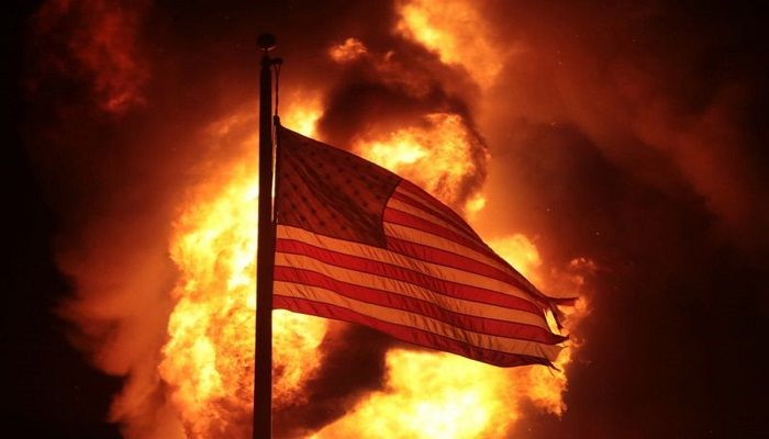 A flag flies in front of a Department of Corrections building, after it was set alight during the second night of unrest in Kenosha, in the US state of Wisconsin. Violent protests followed the police shooting of Jacob Blake, who was shot several times in the back, as he got into a car with his three children inside, on 23 August.