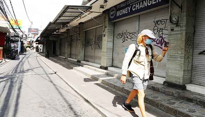 A foreign tourist walks along an empty road lined with closed shops in Bali, Indonesia. Photo: Collected