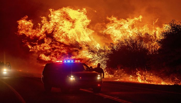 Flames lick above vehicles on Highway 162 as the Bear Fire burns in Oroville, California, on September 9, 2020.