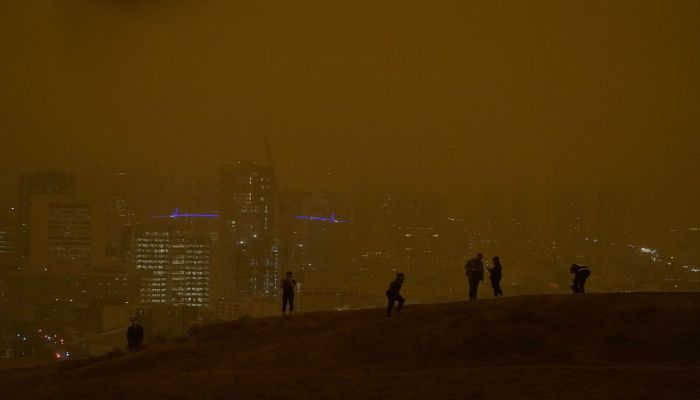 People look toward the skyline obscured by wildfire smoke during daytime, seen from Kite Hill Open Space in San Francisco, on September 9, 2020