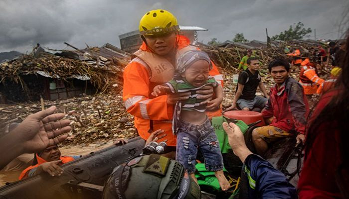 A rescuer carries a young child as floodwaters rise in a village in Rodriguez, Rizal province, Philippines. Typhoon Vamco has battered the country with torrential rain and strong winds, killing at least 39 people and causing widespread destruction.