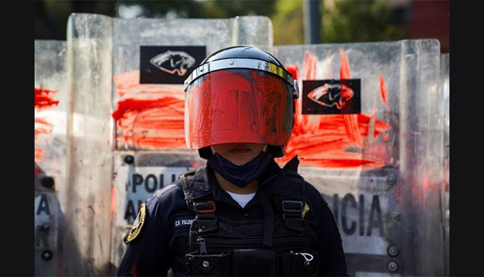 A riot police officer in Mexico City had her helmet visor painted red by a member of a feminist collective, during a protest against gender-based violence in the country.