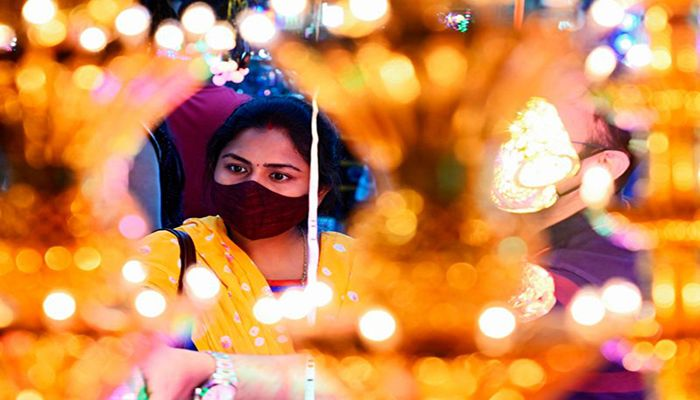 A woman shops for decorative items at a roadside market ahead of Diwali, in Kolkata, India. The five-day festival of lights is celebrated across the world by millions of Hindus and Jains, who traditionally illuminate their homes with candles and lanterns.