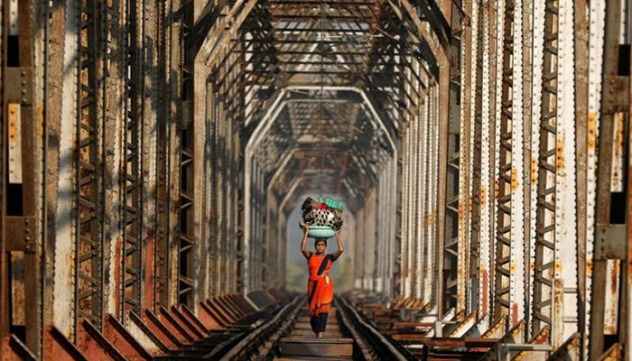 A woman carries luggage along a railway track on the outskirts of Mumbai, India.