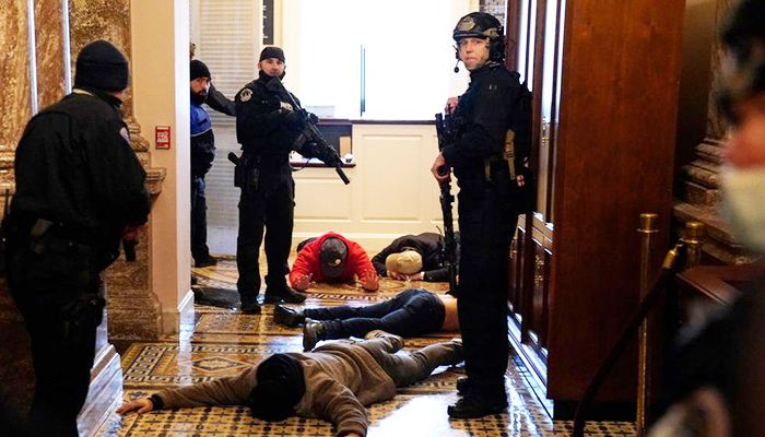 Several protesters are detained by heavily-armed police. Photo: Collected from Reuters