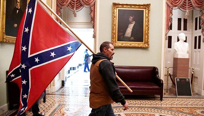 A protester carries the Confederate flag after breaching US Capitol security. Photo: Collected from Reuters