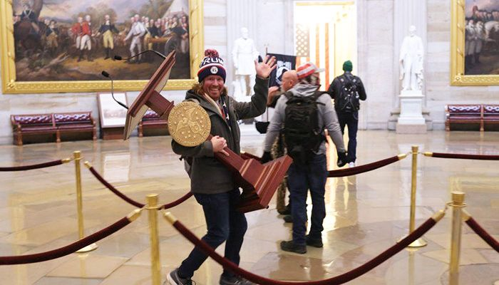 One protester is seen carrying a plinth from a room at the US Capitol. Photo: Collected from Reuters