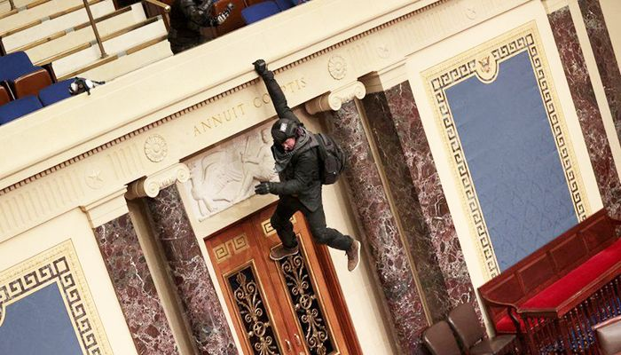 A protester jumps over a balcony to reach the Senate floor. Photo: Collected from Reuters