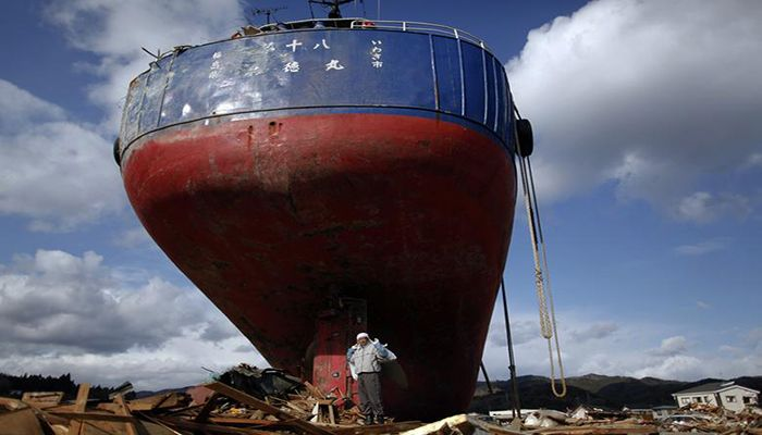A man, carrying belongings salvaged from his ruined house, stands under a ship brought inland by the tsunami in Kesennuma town, Miyagi prefecture more than two weeks after the area was devastated by an earthquake and tsunami March 27.  Photo: Collected from Reuters