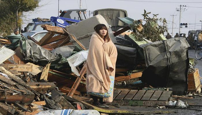 A woman looks at the damage caused by a tsunami and an earthquake in Ishimaki City, Miyagi Prefecture, March 13. Photo: Collected from Reuters