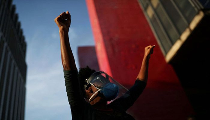 (São Paulo, Brazil) A demonstrator raises her fists during a protest against President Jair Bolsonaro in front of the Museum of Modern Art in São Paulo. || Photograph: Amanda Perobelli/Reuters