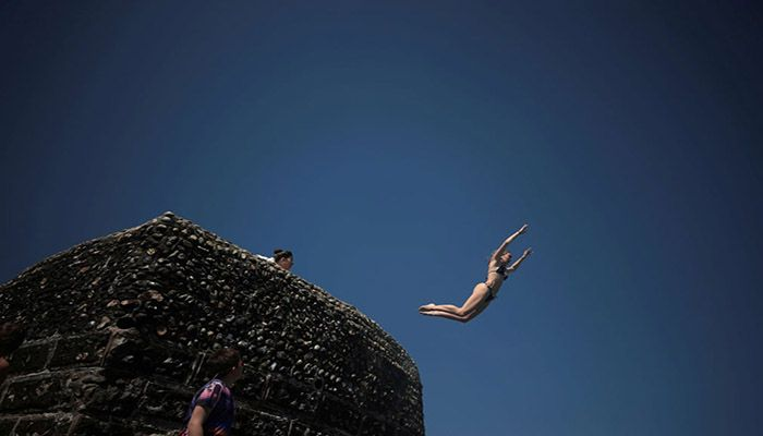 (Brighton, England) A person dives into the sea as people enjoy the hot weather on Brighton beach. || Photograph: Hannah McKay/Reuters