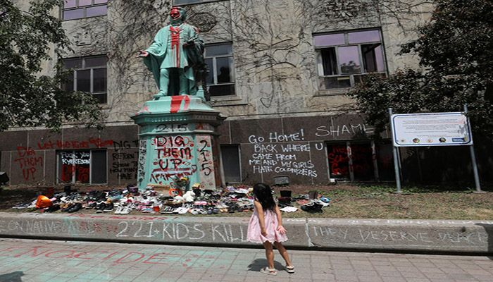 (Toronto, Canada) A girl looks up at the defaced Ryerson University statue of Egerton Ryerson, considered an architect of Canada's residential indigenous school system, following the discovery of the remains of 215 children on the site of British Columbia's former Kamloops Indian Residential school. || Photograph: Chris Helgren/Reuters