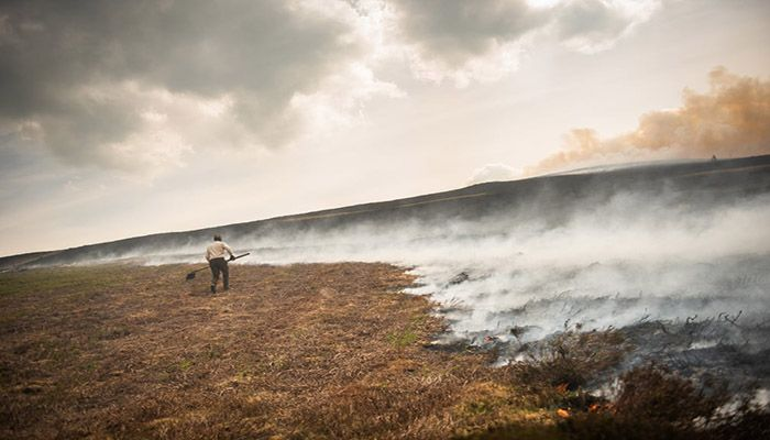 (Llangollen, Wales) Farmer Stephen Frost attempts to beat back a wildfire spreading across the moorland towards his farm above the village of Rhewl in north Wales. || Photograph: Phil Hatcher-Moore/Getty Images