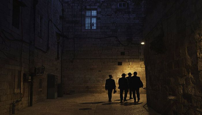 (Jerusalem) Ultra-Orthodox Jewish men walk at night in Jerusalem's Old City days after a ceasefire was reached in the 11-day war between Gaza's Hamas rulers and Israel. || Photograph: Felipe Dana/AP