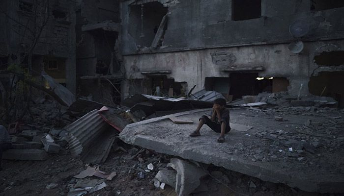 (Beit Hanoun, Gaza) A boy closes his eyes as he plays hide-and-seek at dusk in a neighbourhood heavily damaged by airstrikes during an 11-day war between Gaza's Hamas rulers and Israel. || Photograph: Felipe Dana/AP